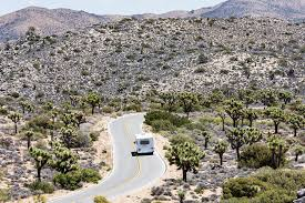 C Class RV driving a desert road toward mountains